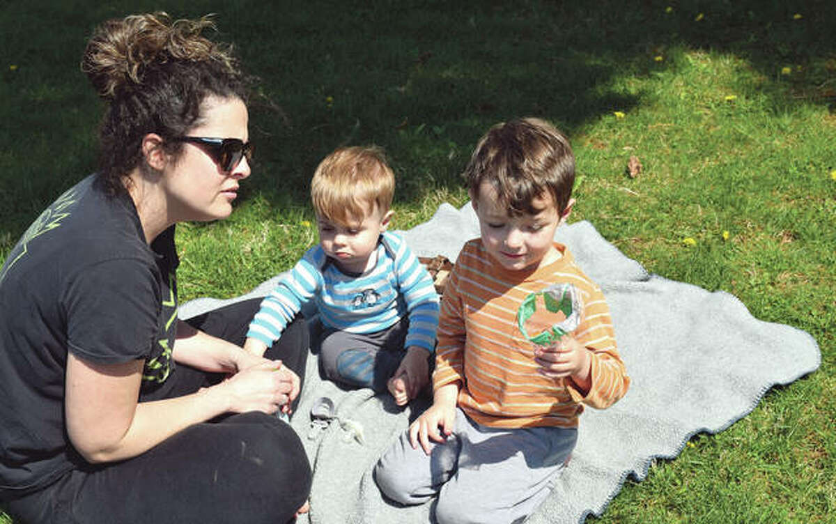 Erin Alloway of Jacksonville has a picnic Monday at Nichols Park with her sons, Thomas, 1, and Colin, 5. The temperature reached almost 70 degrees, but the sunshine and warmth were expected to give way overnight to much colder temperatures and the potential for snow today.