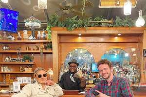 Veteran Hattie's Restaurant bartender Sal Porterfield, center, shows off the funds the Saratoga Springs restaurant received through the local website Two Buttons Deep's Big Tip Energy campaign, with 2BD co-founders Taylor Rao, left, and Jack Carpenter. (Provided photo.)
