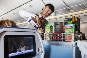 Aeroplane Inflight Cabin Attendent Serving Drinks (Photo by: Dukas/Universal Images Group via Getty Images)