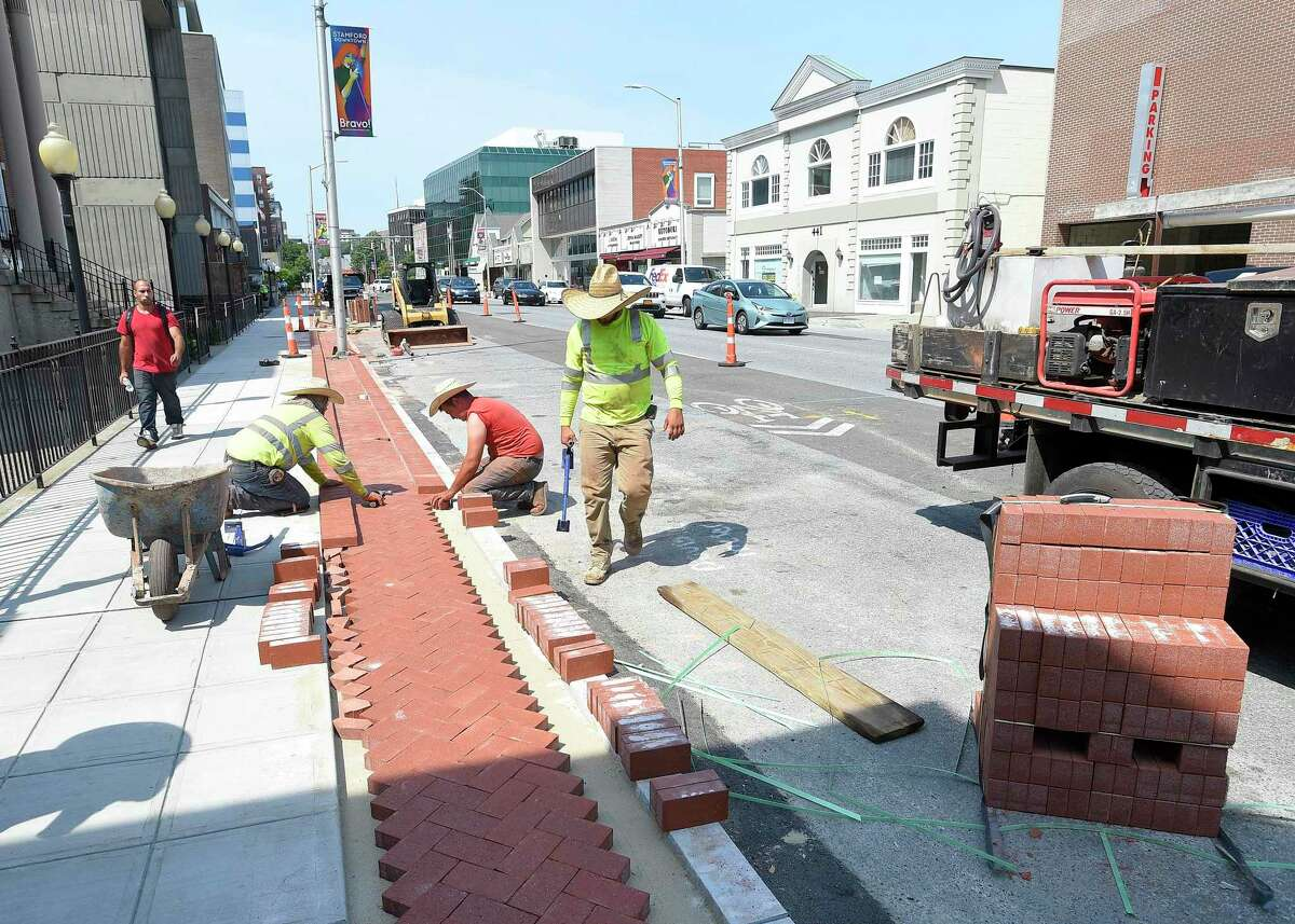 A crew from Colonna Concrete and Asphalt Paving out of West Haven lay out a decorative edging to a new sidewalk along Summer Street in Stamford, Conn. on July 16, 2019. The crew of four each were wearing large straw caps to help shade themselves from the heat of the sun. Temperatures in the region reach into the 90's with no expected relief in the coming days.