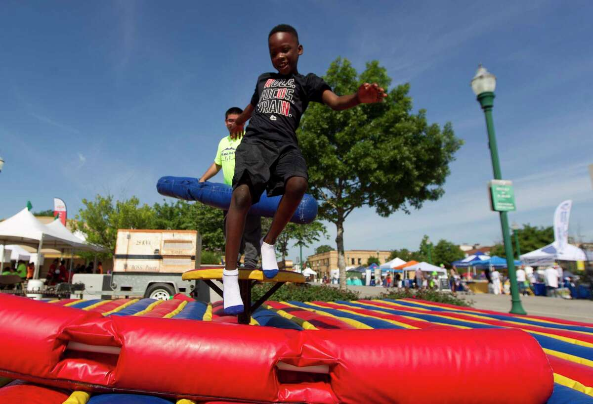 Kahiden George, right, laughs is knocked down off a podium as he plays game during the annual KidzFest in downtown Conroe, Saturday, April 28, 2018.This year's event is set for Saturday.