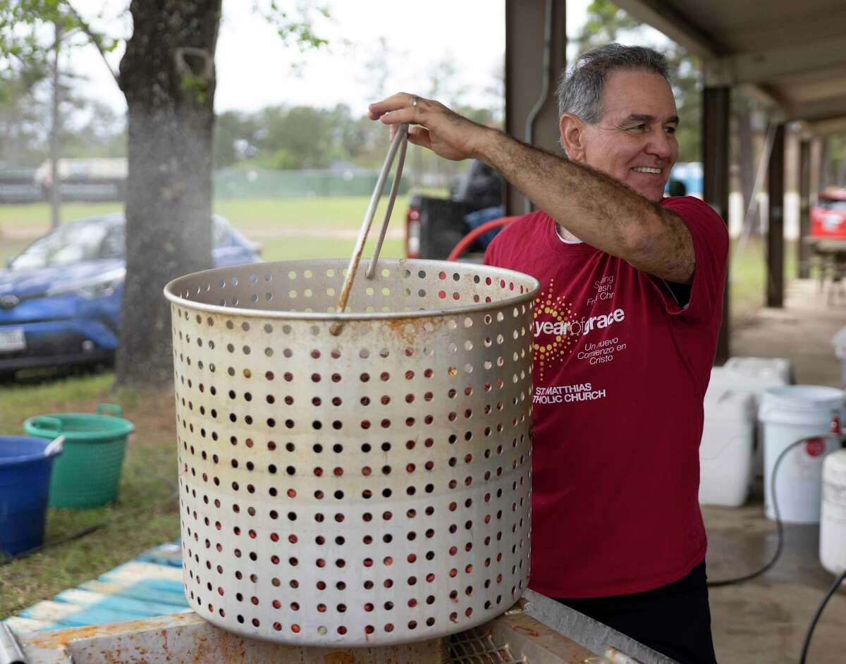 John Mattern shares a smile as he prepares to load crawfish into a broiler during a crawfish boil fundraiser at St. Matthias Catholic Church, Saturday, April 17, 2021, in Magnolia. Volunteers prepared over 825 lbs of crawfish and 220 lbs of shrimp. Funds raised will be used for the cost of their new church.