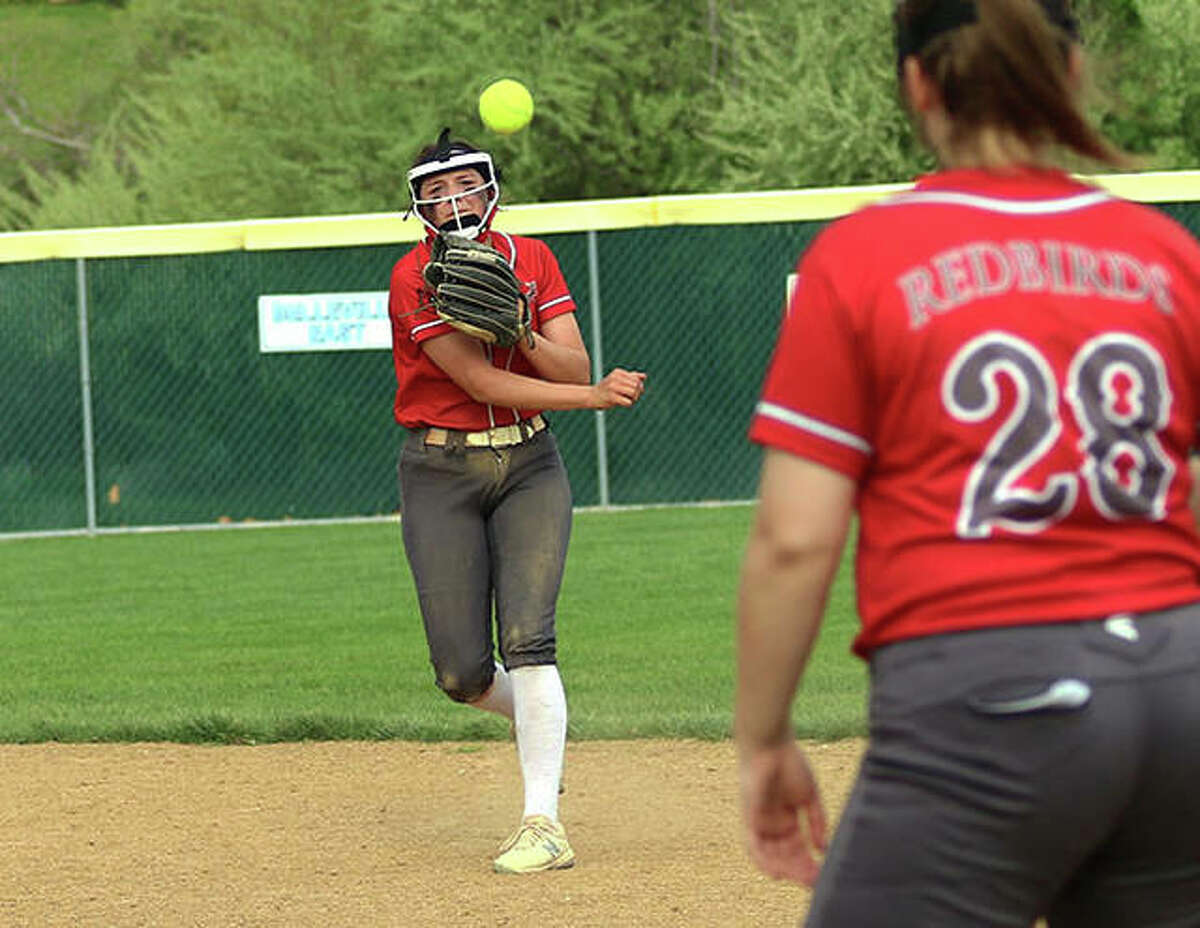 Alton second baseman Alissa Sauls (left) throws to first baseman Olivia Ducey for an out Monday against Triad at Alton High in Godfrey.
