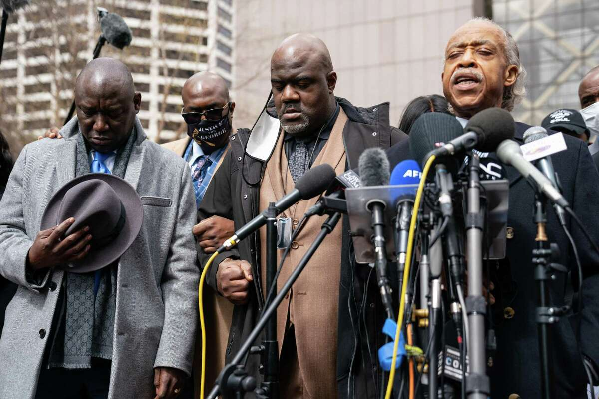 The Rev. Al Sharpton, right, Philonise Floyd, center, and attorney Ben Crump, left, along with others, lead the family of George Floyd and Daunte Wright in prayer outside the courthouse during closing arguments in the Derek Chauvin trial on Monday, April 19, 2021, in Minneapolis. (Jason Armond/Los Angeles Times/TNS)