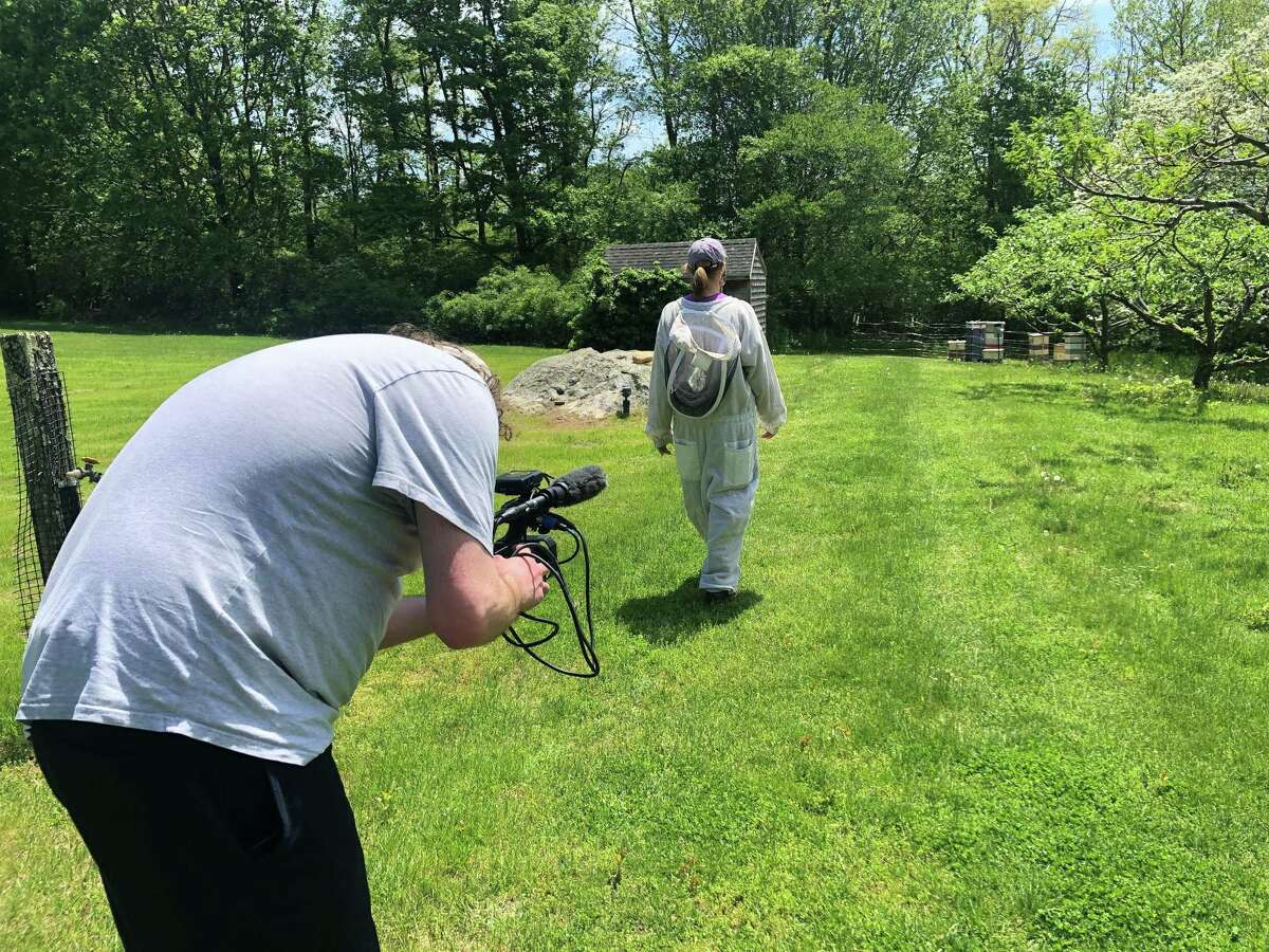 """Chris Sinise, of Stratford and a graduate student at Pace University, films a local beekeeper for the documentary """"Bee Aware,"""" which premieres online on Earth Day."""