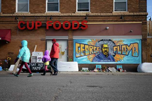 People walk past a memorial for George Floyd outside Cup Foods market in Minneapolis, Minn., on Tuesday, April 20, 2021. Photo: Christian Monterrosa / Bloomberg / © 2021 Bloomberg Finance LP