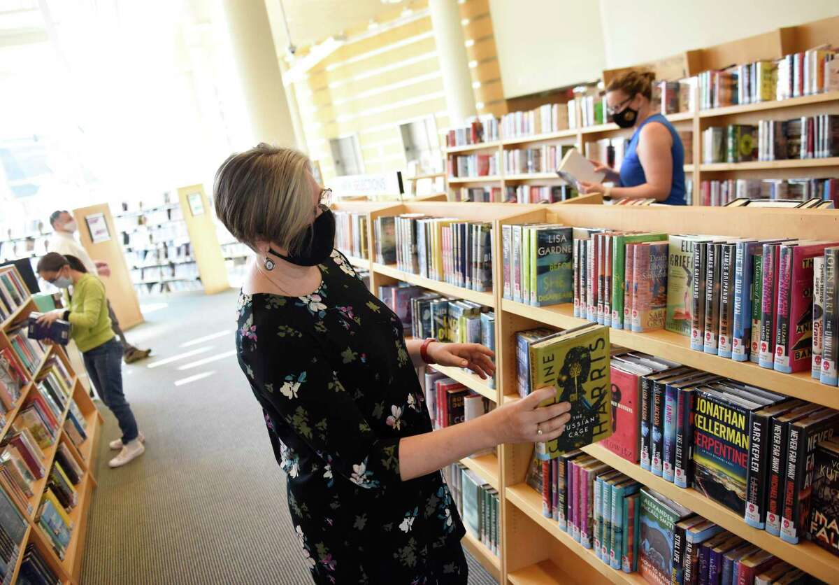 Information Services Manager Kate Soboleva browses new releases at the Greenwich Library in Greenwich, Conn. Tuesday, April 20, 2021. More than a year after it was forced to close its doors due to the COVID-19 pandemic, Greenwich Library has welcomed back the public by appointment only for 20 minute visits. Patrons will be welcomed back to the library's sleek new look, which includes a new cafe and major interior renovations.