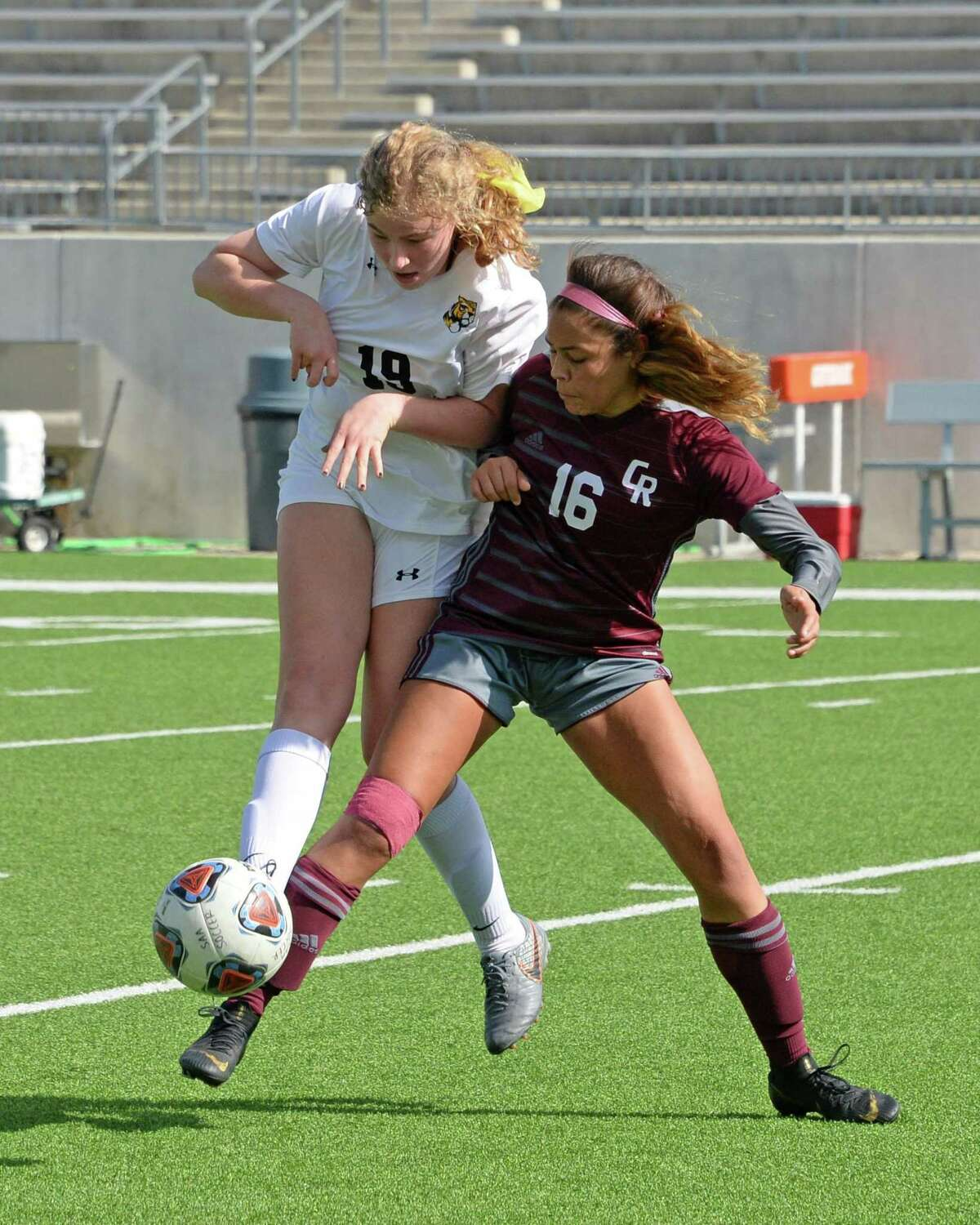 Sara Price (19) of St. Agnes and Junel Quintero (16) of Cinco Ranch compete for a ball during the first half of a high school soccer game between the Cinco Ranch Cougars and the St. Agnes Tigers in the Cougar Bracket final of the I-10 Shootout on Saturday, January 11, 2020 at Legacy Stadium, Katy, TX.