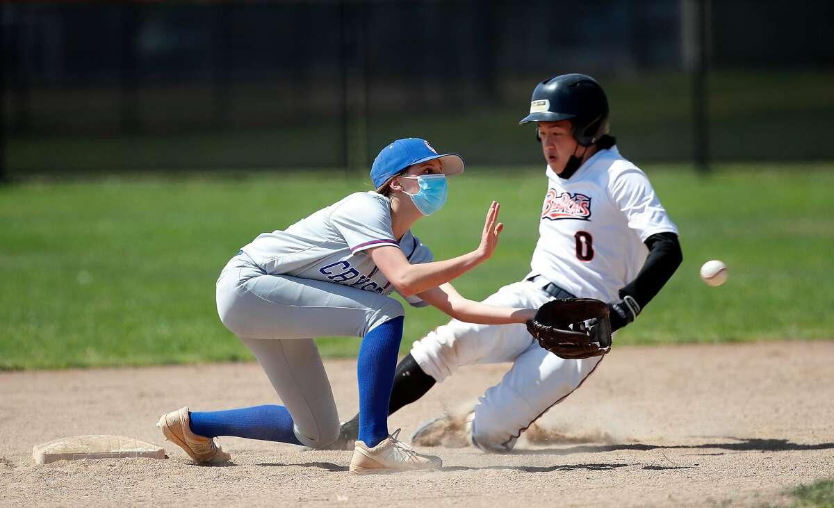 Crystal Springs varsity baseball player Maddie Etheridge (8) fields the ball as San Mateo High Edward Huang (0) slides safety to second base during game at San Mateo, California on Saturday, April 10, 2021.