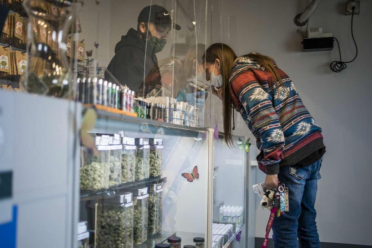Steven Vechanko, a shift lead at CannaBay Recreational & Medical Marijuana Dispensary, left, allows Amanda Bastian of Bay City, right, to sniff a strain of marijuana as she makes a purchase Tuesday, April 20, 2021 at the dispensary on N. Sherman Street in Bay City.