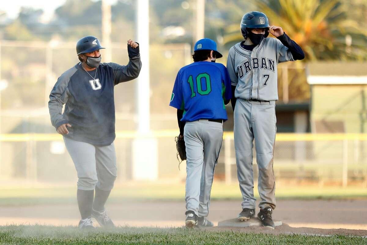 Urban School coach Oz Sailors celebrates after Harrison Sharp-Craig steals third in a game against San Domenico High.