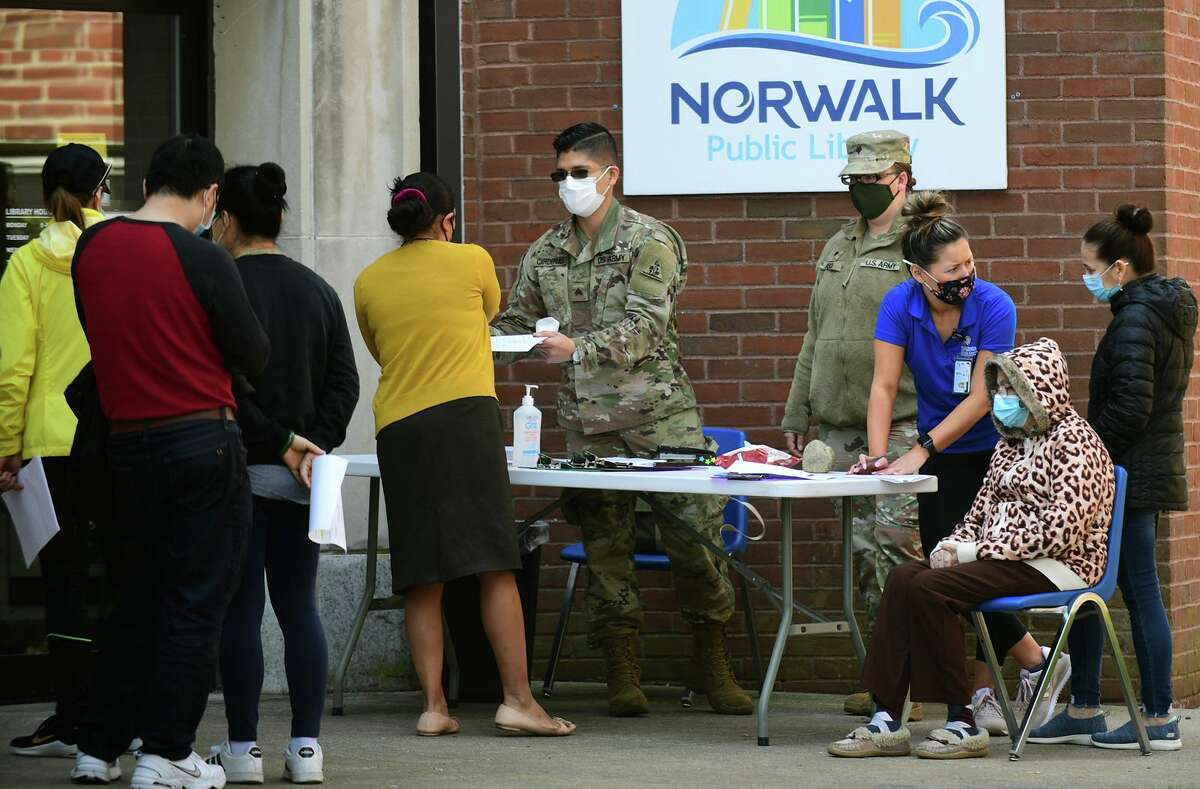 National gurad troops help as local residents line up for the The Griffin Hospital mobile COVID-19 vaccination clinic at the Norwalk Public Library main branch on Belden Ave. Tuesday, April 20, 2021, in Norwalk. Appointments are not required for the vaccination clinic and walk-up patients are encouraged to attend, Morgan said. Two mobile units plan to administer up to 250 vaccines a day, with more than 1,000 vaccines administered during the five-day stay.