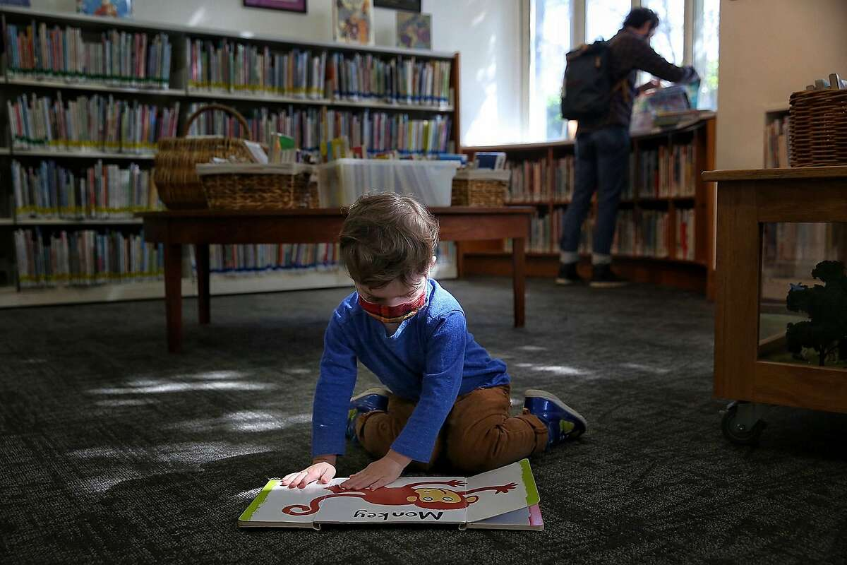 Frank, 2, opens flaps of a book as father Shawn (background) browses at the Rockridge branch of the Oakland library.