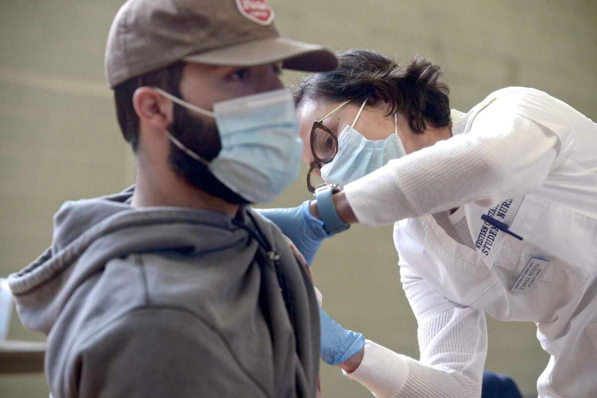 Nursing student Evania Reisen, right, administers a COVID-19 vaccination to fellow Western Connecticut State University student Zak Santoemma, of Madison, during a vaccination clinic at the university in Danbury, Conn., in April 2021.