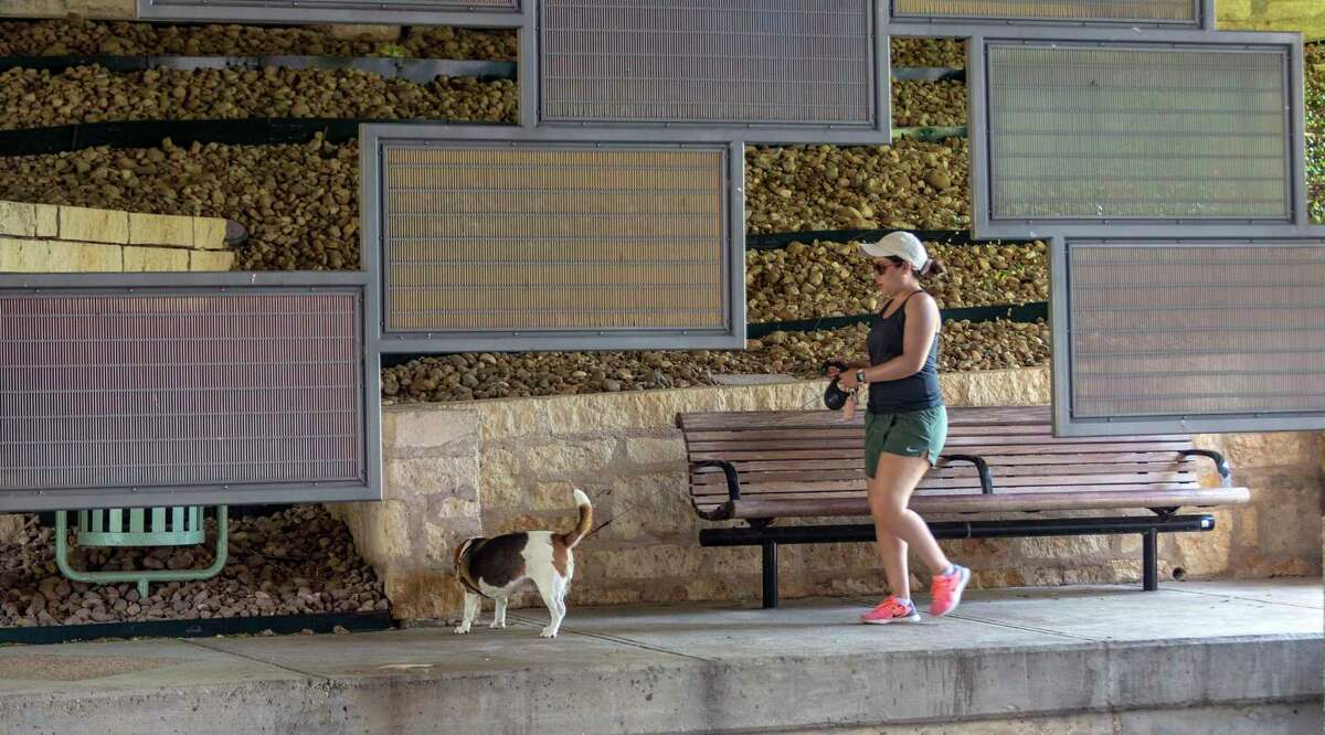 """A stroller walks her dog past the art installation """"29 degrees 25' 57"""" N/98 degrees 29' 13"""" W"""" and """"29 degrees 26' 00"""" N/ 98 degrees 29' 07"""" W"""" on the Museum Reach of the San Antonio River Walk."""