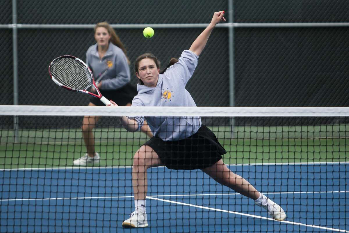 Midland's Grace Lloyd, right, competes in a #1 doubles match, alongside partner Emily Genau, left, against opponents from Flint Powers Tuesday, April 20, 2021 at the Greater Midland Tennis Center. (Katy Kildee/kkildee@mdn.net)