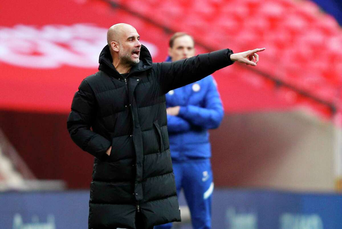 Manchester City's head coach Pep Guardiola gives instructions during the English FA Cup semifinal soccer match between Chelsea and Manchester City at Wembley Stadium in London, England, Saturday, April 17, 2021.
