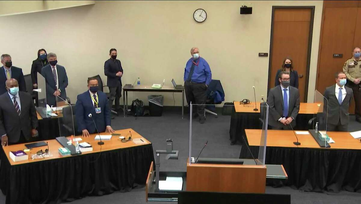 In this image from video, defense attorney Eric Nelson, and defendant, former Minneapolis police Officer Derek Chauvin, both on the right side of the courtroom, arrive for the verdict in Chauvin's trial for the 2020 death of George Floyd, Tuesday, April 20, 2021, at the Hennepin County Courthouse in Minneapolis, Minn. Behind the front table at left is prosecutor Jerry Blackwell. Behind the rear table at left is prosecutor Steve Schleicher, left, and Assistant Minnesota Attorney General Matthew Frank. (Court TV via AP, Pool)