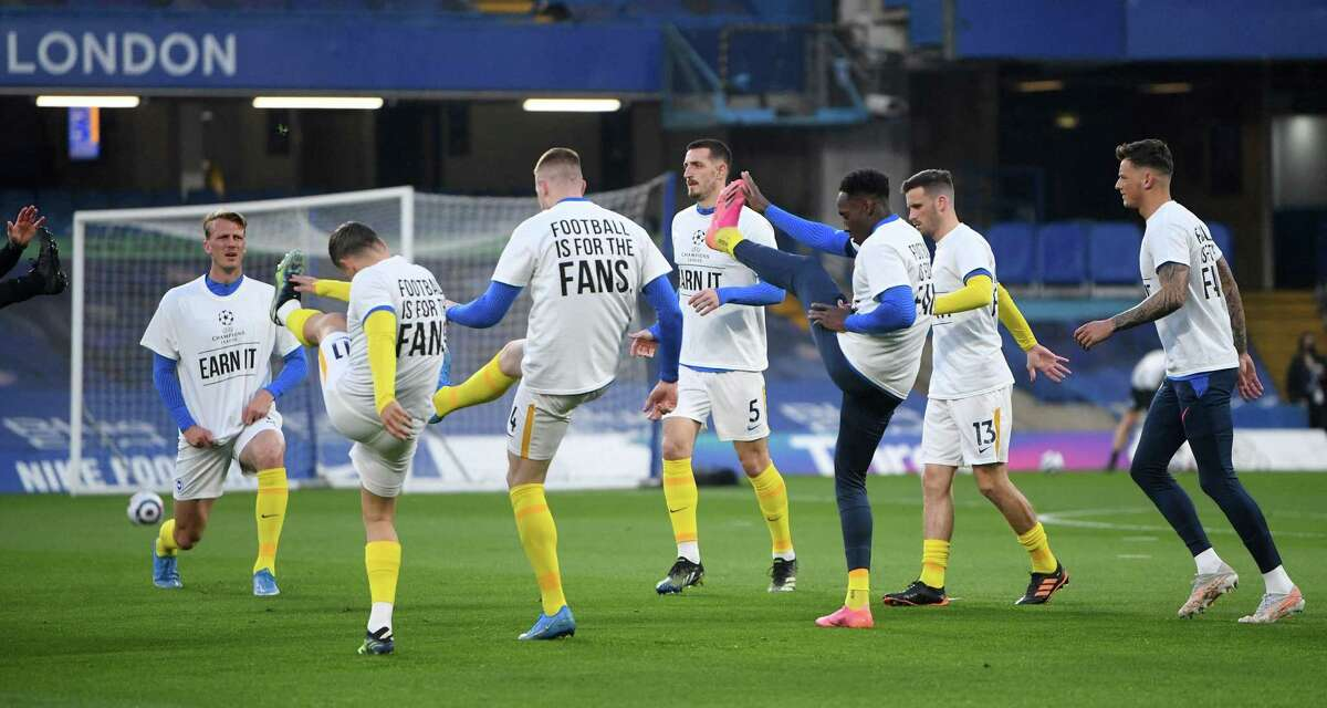 Brighton players wear anti-European Super League T-shirts as they warm up before a match against Chelsea on Tuesday at Stamford Bridge stadium in London.