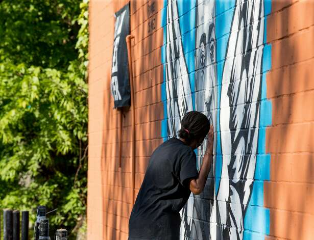 Sheila Masters hugs a George Floyd mural near Cuney Homes, following the guilty verdict on all counts in the murder trial of former Minneapolis Officer Derek Chauvin, on Tuesday, April 20, 2021, in Third Ward, Houston. Photo: Godofredo A. Vásquez/Staff Photographer / © 2021 Houston Chronicle