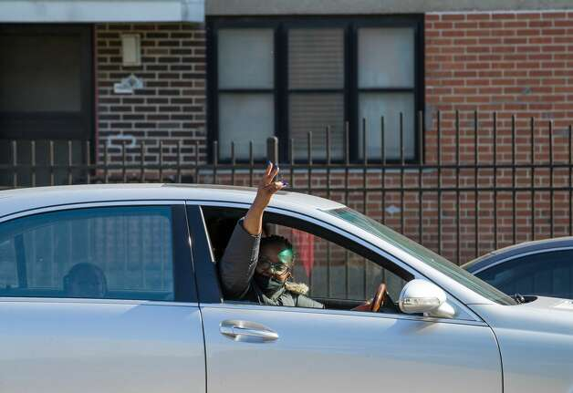 """A woman exclaims """"Justice for George Floyd"""" while driving past Cuney Homes, following the guilty verdict on all counts in the murder trial of former Minneapolis Officer Derek Chauvin, on Tuesday, April 20, 2021, in Third Ward, Houston. Photo: Godofredo A. Vásquez/Staff Photographer / © 2021 Houston Chronicle"""