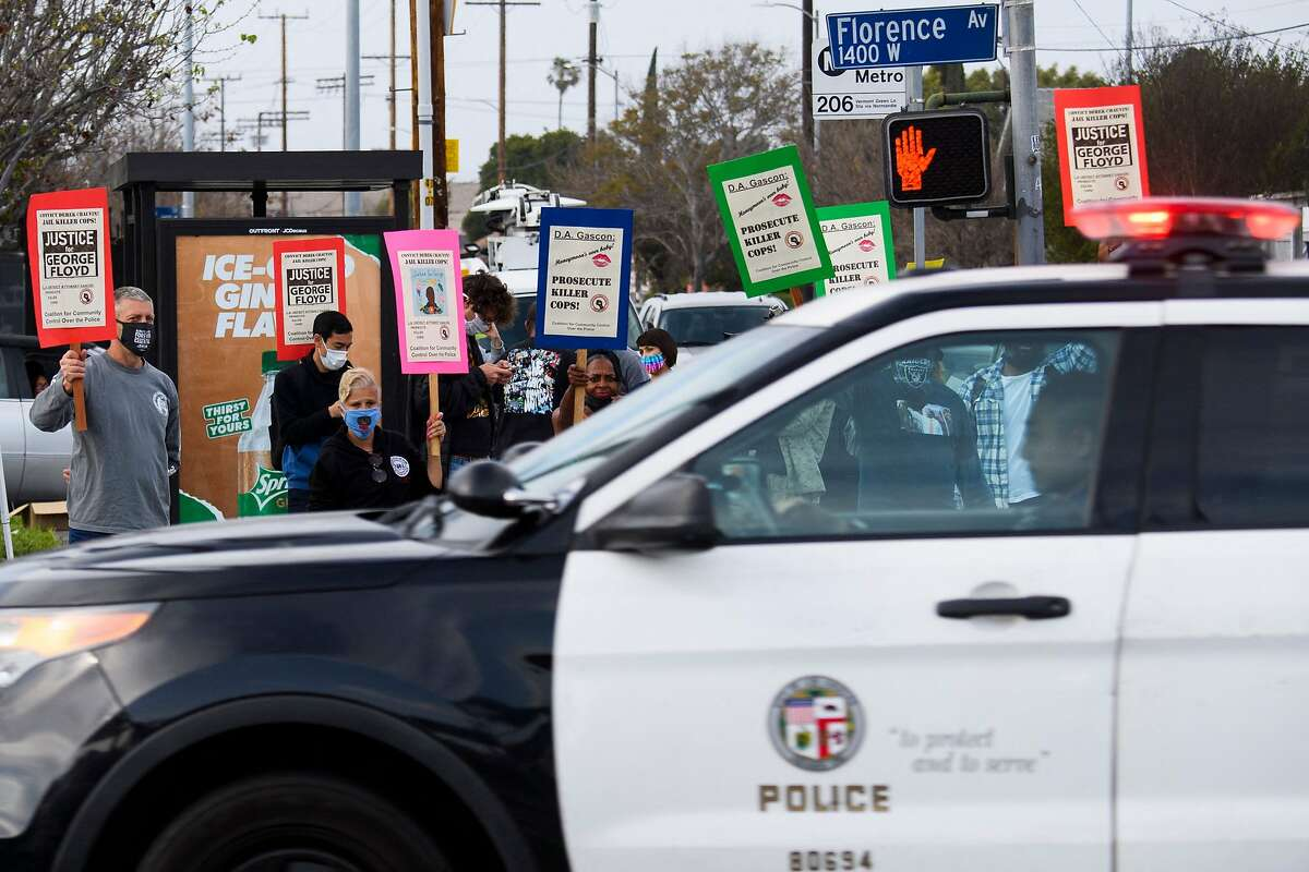 A Los Angeles police car drives past as people protest the killings of people by police, including the deaths of George Floyd and Daunte Wright, on April 12.