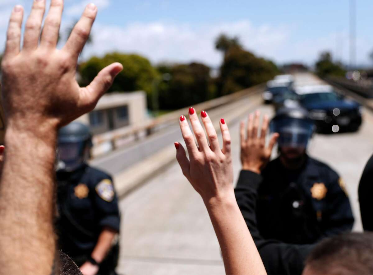 Anti-police brutality protesters hold their hands up as California Highway Patrol officers block their march on Interstate 880 in Oakland in June.