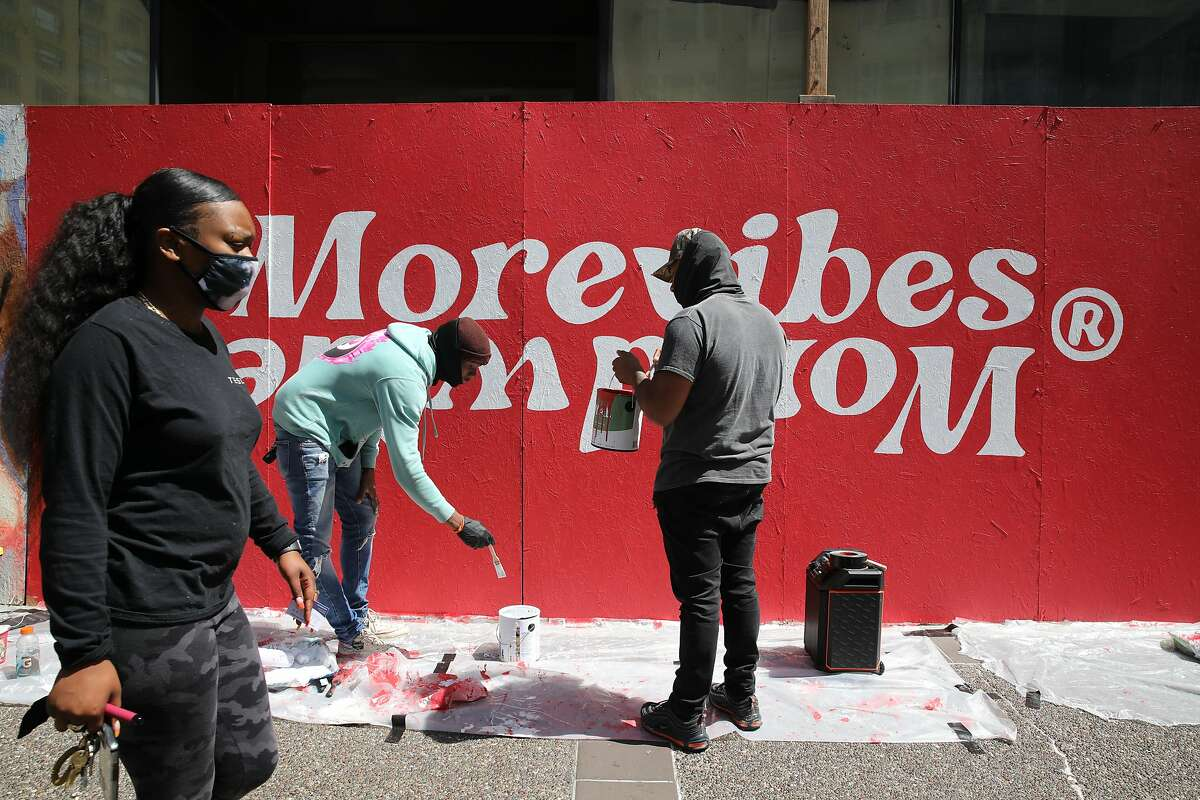 Daghe, 36, of Oakland, co-founder of art collective More Vibes, left, and Kalani Ware, 32, of Oakland, visual artist, paint a mural after a jury in Minneapolis found former police officer Derek Chauvin guilty of George Floyd's death in Oakland, Calif. on Tuesday, April 20, 2021. The artists listened to the verdict from a speaker.