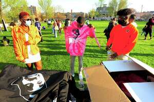Nasair Dublin, center, checks out a pink hoodie to buy during Max Antoine Day, a memorial and anti-gun rally for the late Stamford resident killed in 2017, at Jackie Robinson Park in Stamford, Conn., on Tuesday April 20, 2021. At left is Max's daughter Cheyenne Antoine. After issuing a proclamation to the event, Mayor David Martin addressed Stamford's most recent bout of gun violence.