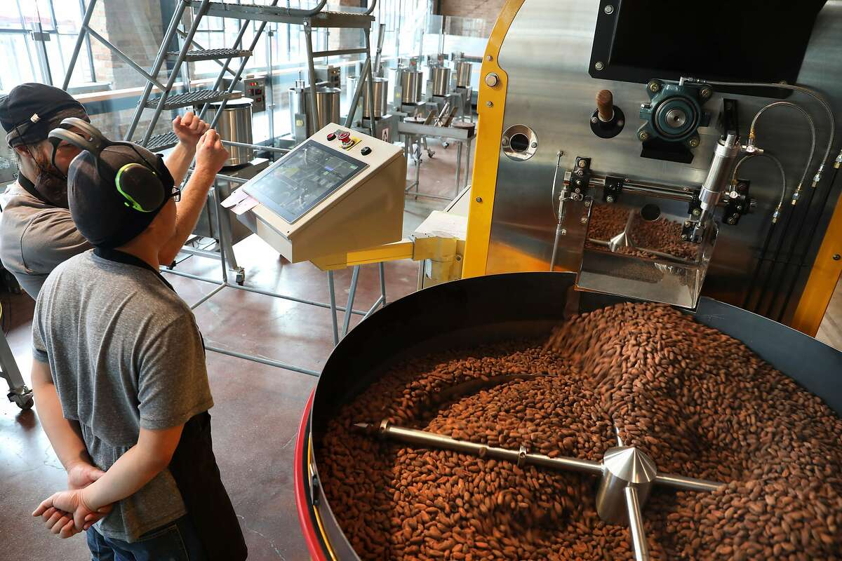 Chocolate makers Bryan O'Connell (back left) and Eric Chain (front left) take just roasted seeds out of machine on the main factory floor of Dandelion's brand-new chocolate factory on Thursday, April 4, 2019, in San Francisco, Calif.