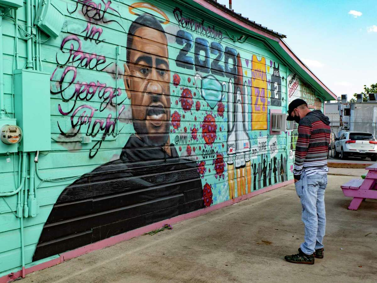 Ryan Angermiller prays at the George Floyd mural located at Big Poppa's restaurant at Interstate 35 and New Braunfels shortly after the police officer that killed Floyd in Minneapolis on May 25, 2020 was convicted of his murder on Tuesday, April 20, 2021. Angermiller drove in from Hondo to pay his respects.