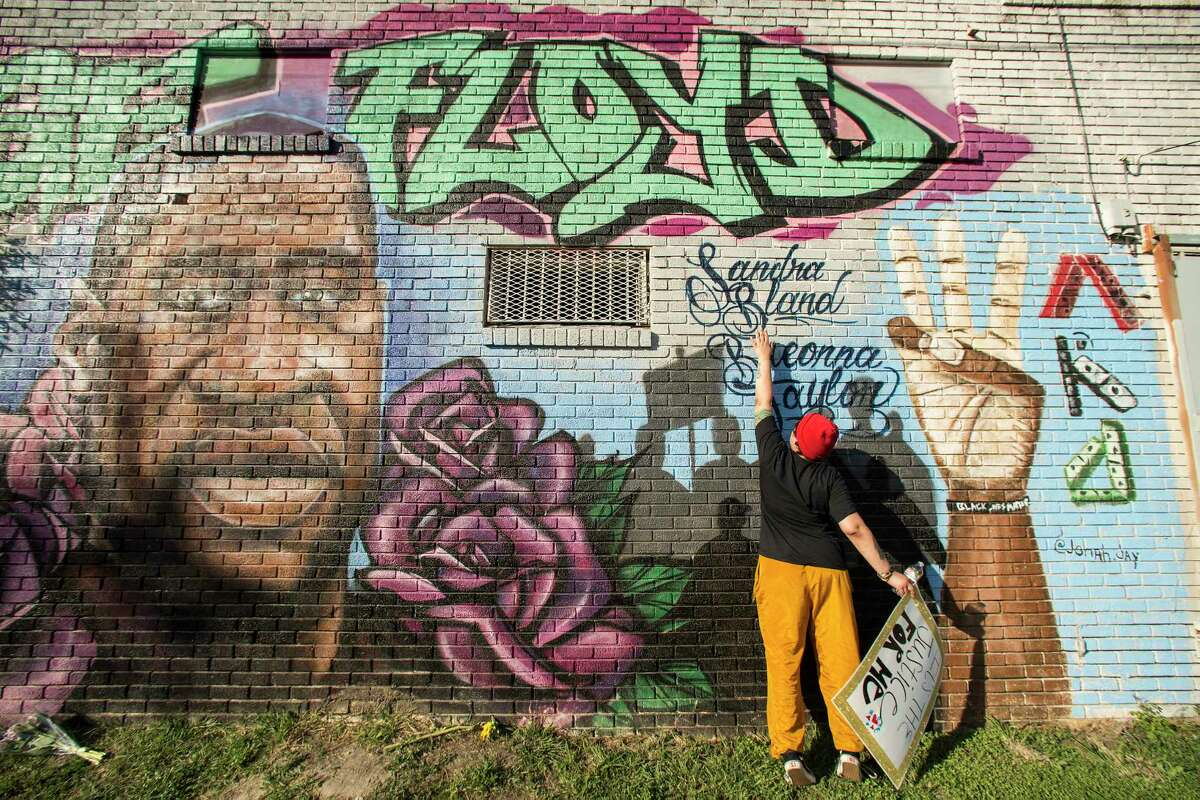 """Daryel Simmons reaches up to touch the names of Sandra Bland and Breonna Taylor as she came to a George Floyd memorial mural near the intersection of Ennis and Elgin as she joins others as people react after learning of the guilty verdict on all counts in the murder trial of former Minneapolis Officer Derek Chauvin in the death of George Floyd on Tuesday, April 20, 2021, in Houston. """"It's a joyous day,"""" Simmons said as she celebrated the verdict."""