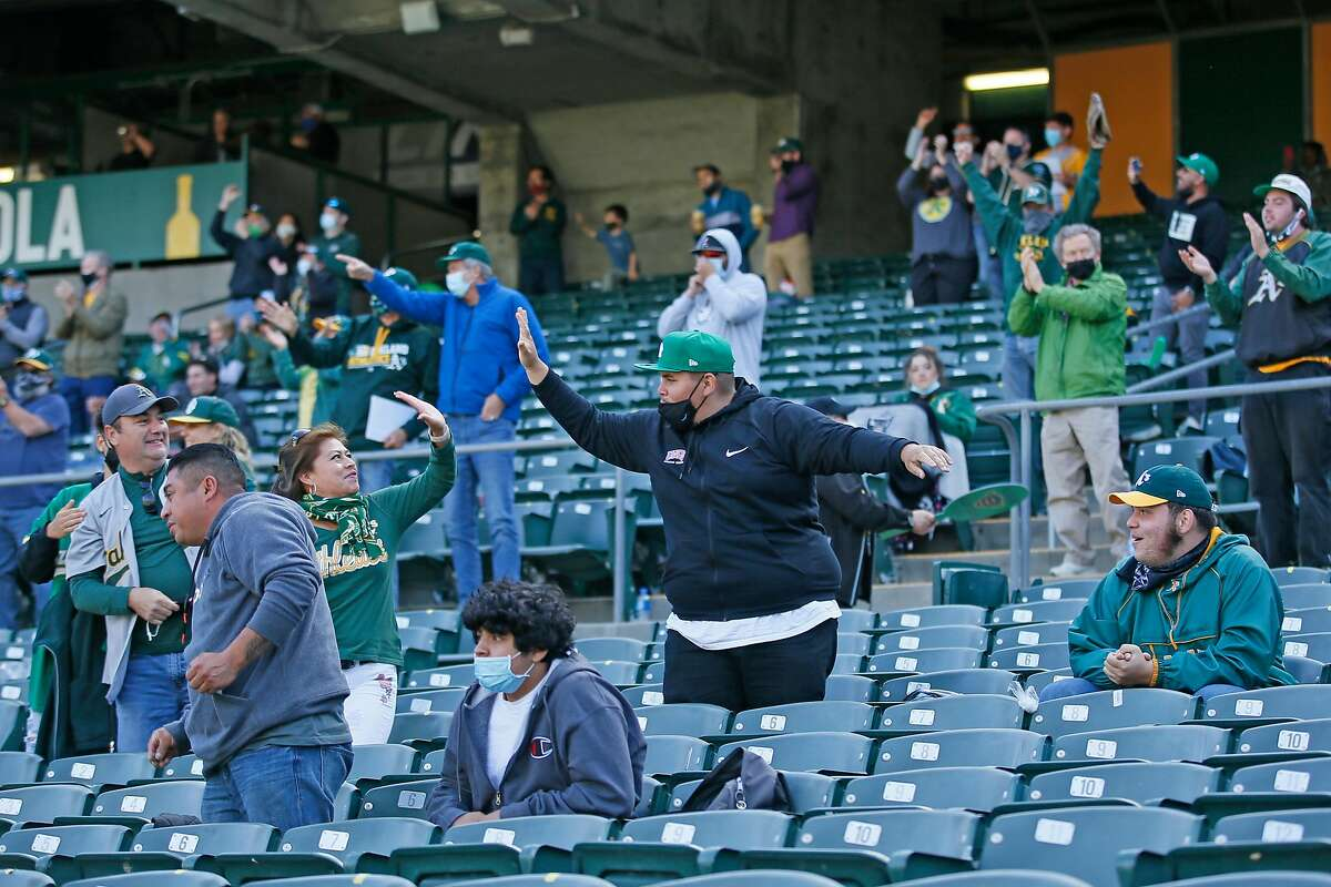 A's fans celebrate Matt Olson's fourth-inning grand slam in Tuesday's first game against the Twins.