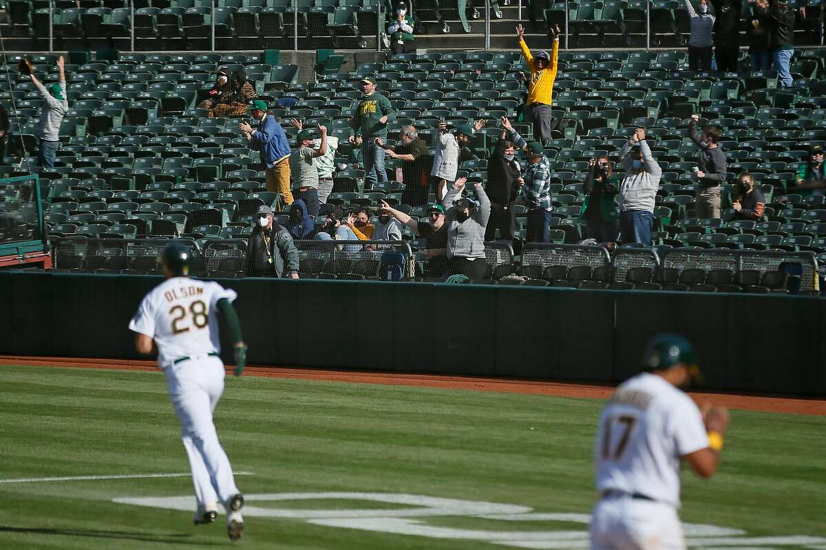 Fans reacts to the grand slam of Oakland Athletics first baseman Matt Olson (28) in the fourth inning during the first game of an MLB doubleheader against the Minnesota Twins at RingCentral Coliseum on Tuesday, April 20, 2021, in Oakland, Calif.