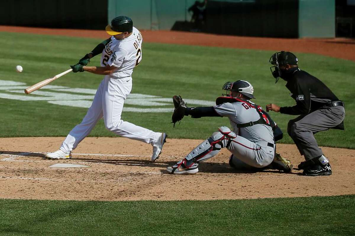 Oakland Athletics first baseman Matt Olson (28) hits a grand slam in the fourth inning during the first game of an MLB doubleheader against the Minnesota Twins at RingCentral Coliseum on Tuesday, April 20, 2021, in Oakland, Calif.