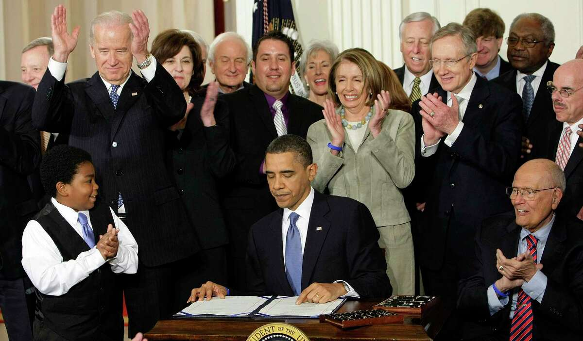 President Barack Obama signs the Affordable Care Act in 2010. President Joe Biden, then the vice president, has long been a strong supporter of the act.