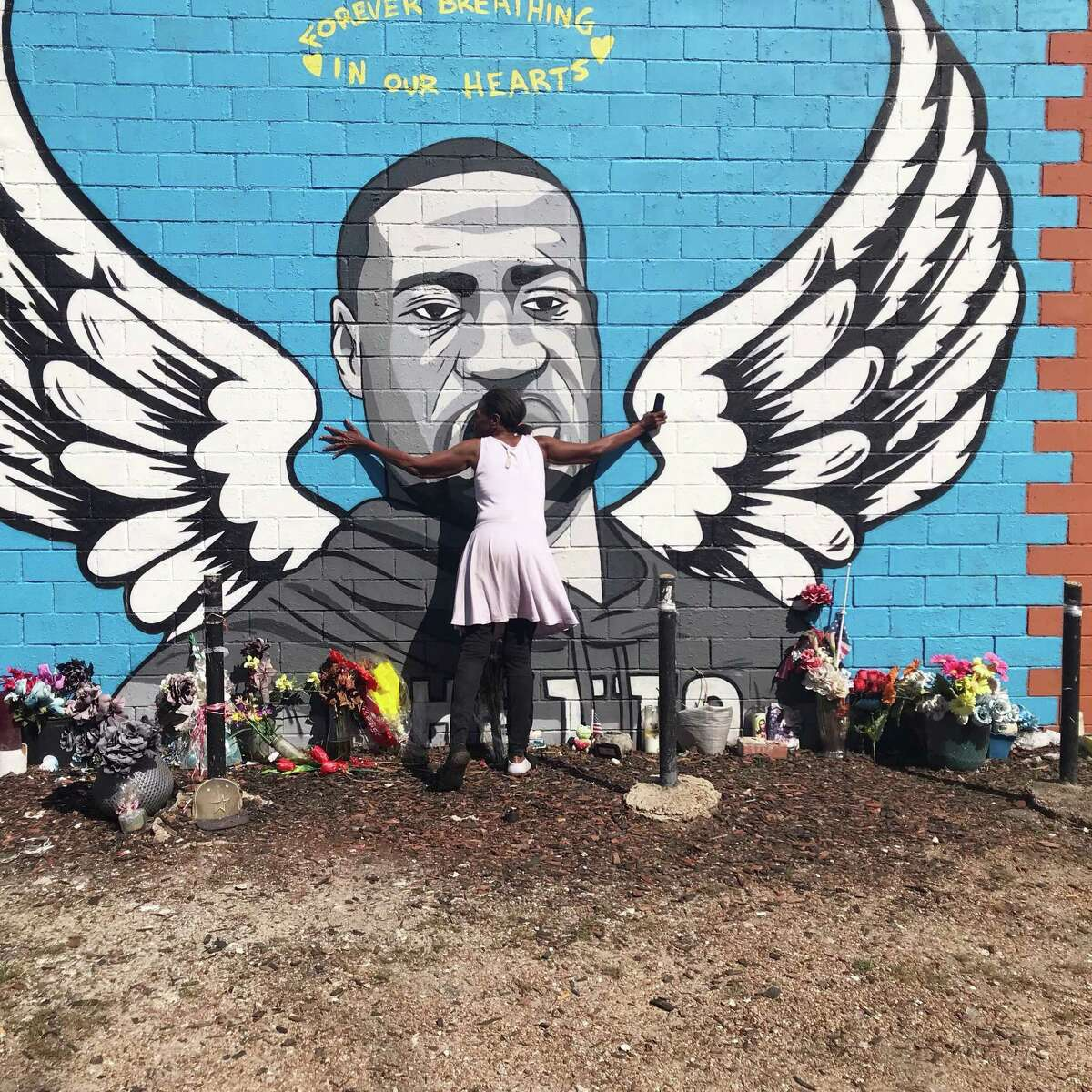 Sheila Masters hugs a mural of George Floyd in Third Ward Tuesday afternoon after a jury found Derek Chauvin, the officer who killed Floyd, guilty of second degree murder, third degree murder and manslaughter.