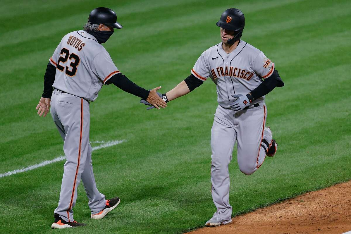 The Giants' Buster Posey celebrates with third base coach Ron Wotusthe in the fifth after hitting the first of his two home runs during the victory. Posey had three on the