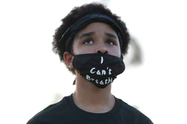 """Jillian Williams wears a mask that reads """"I can't breathe"""" during a vigil at MacGregor Park after they learned the guilty verdict on all counts in the murder trial of former Minneapolis Officer Derek Chauvin in the death of George Floyd on Tuesday, April 20, 2021, in Houston. Photo: Karen Warren, Staff Photographer / @2021 Houston Chronicle"""