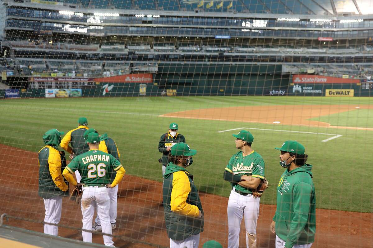The Oakland Athletics wait out a game delay in the fifth inning during the second game of an MLB doubleheader against the Minnesota Twins at RingCentral Coliseum on Tuesday, April 20, 2021, in Oakland, Calif. The sudden power loss of the left field light bank prompted the delay of game.