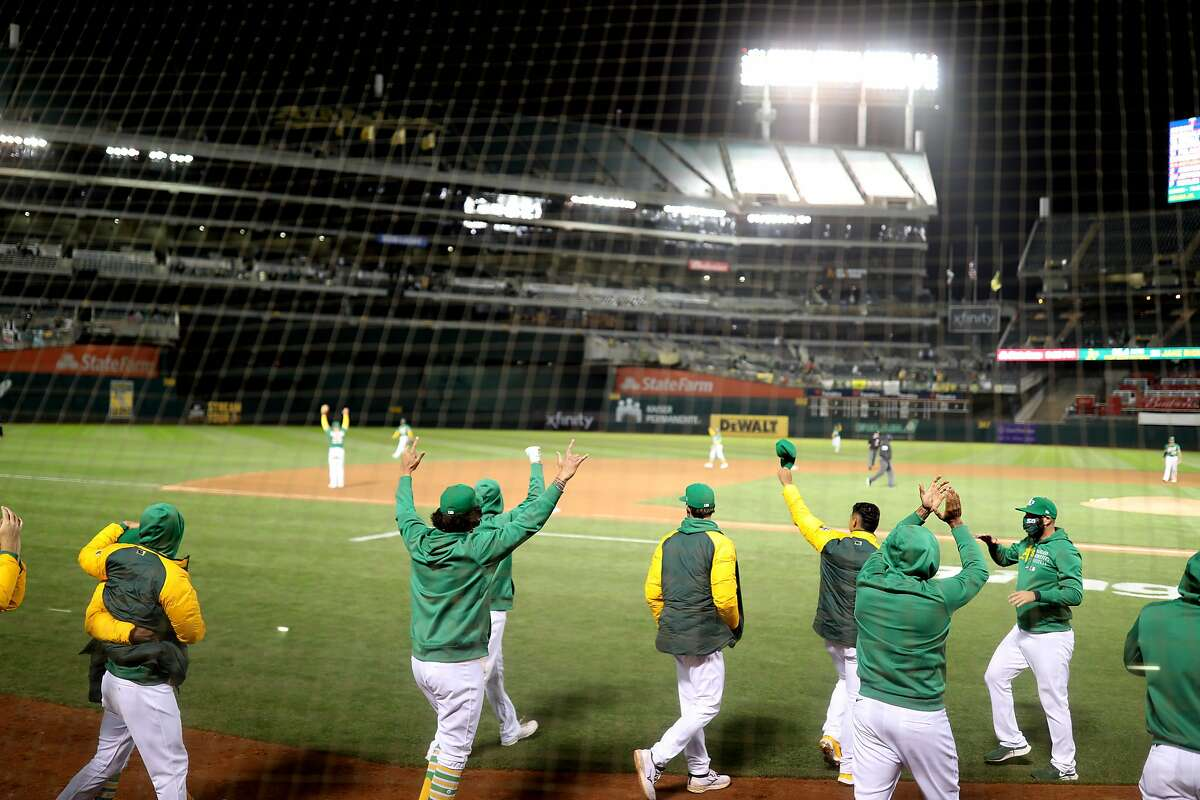 The dugout runs out after Oakland Athletics left fielder Mark Canha (20) makes the final out for the win against the Minnesota Twins in the second game of an MLB doubleheader at RingCentral Coliseum on Tuesday, April 20, 2021, in Oakland, Calif. The A's won 1-0.