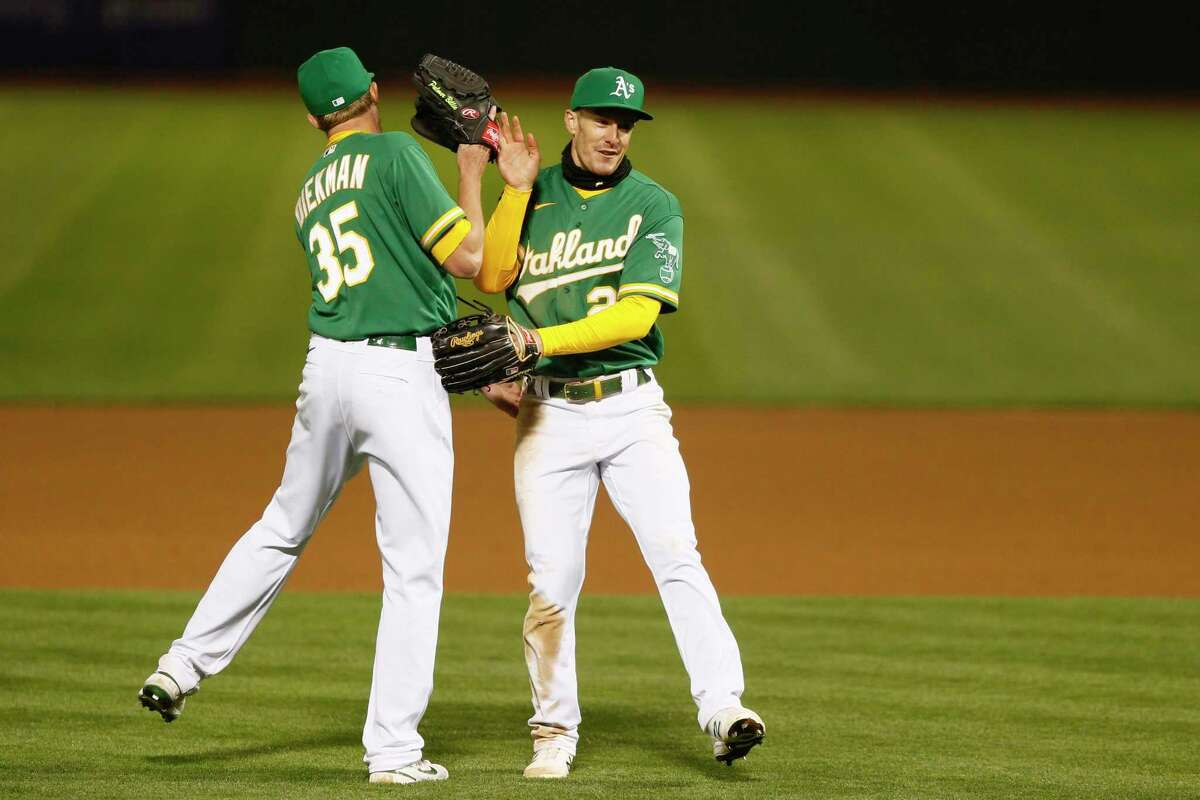 Oakland Athletics left fielder Mark Canha (20) and Oakland Athletics relief pitcher Jake Diekman (35) celebrate the win against the Minnesota Twins in the second game of an MLB doubleheader at RingCentral Coliseum on Tuesday, April 20, 2021, in Oakland, Calif. The A's won 1-0.