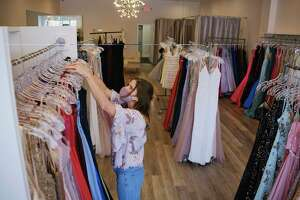 Tara Attanasio, owner of Azalea Dresses, straightens prom dresses hanging at her shop on Tuesday, April 21, 2021, in Guilderland, N.Y. This prom season, Attanasio has only sold one quarter of the prom dresses she would normally sell.    (Paul Buckowski/Times Union)