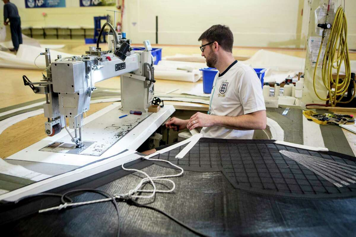 Brian Doyle sews tack webbing onto a sail that is 43 meters tall and 14 meters wide at North Sail in Milford.