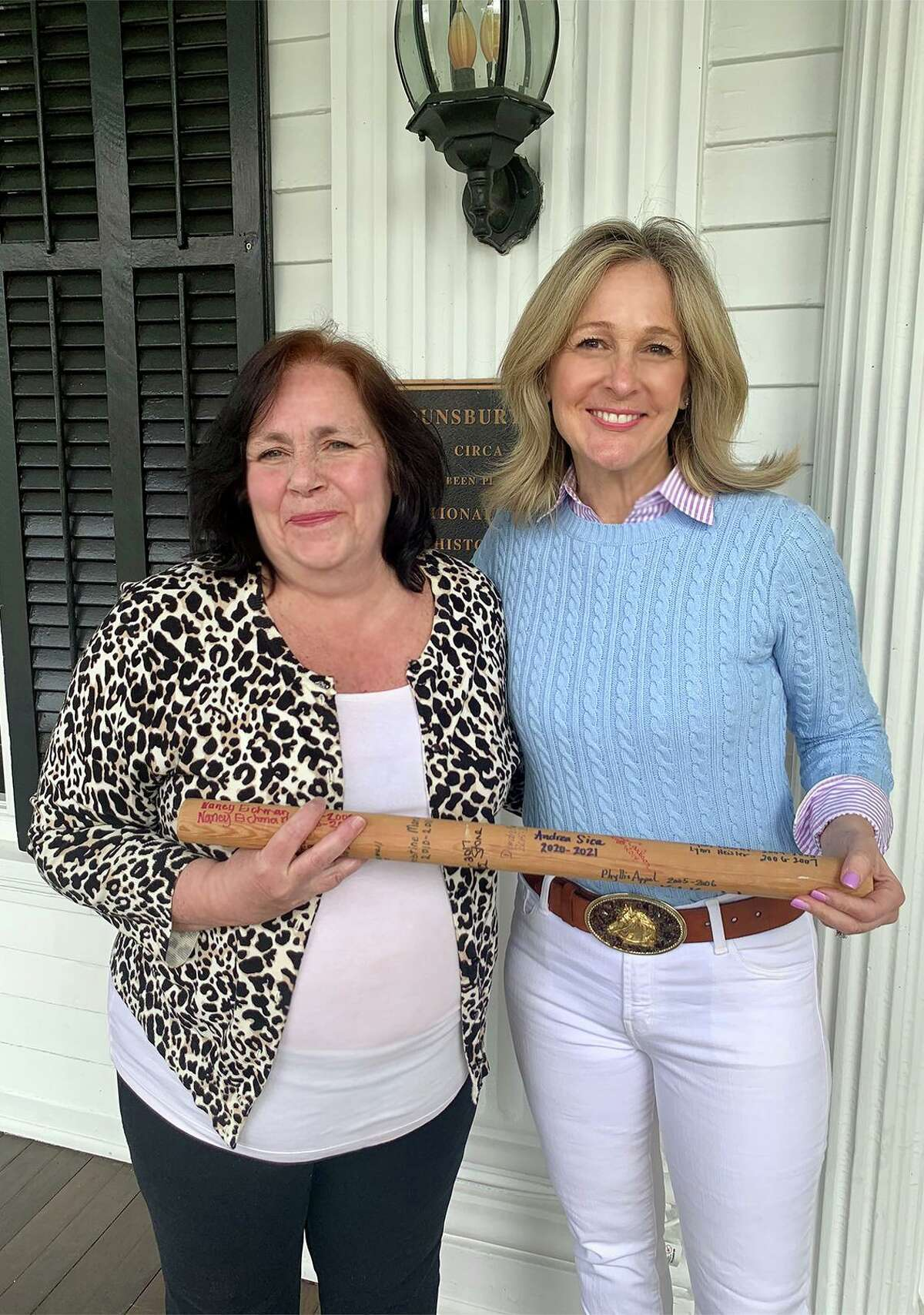LouAnne Cazalet, left, and Andrea Sica hold a baton that is passed from president to president of the National Charity League's Nutmeg Chapter, which is celebrating its 20th anniversary this year.