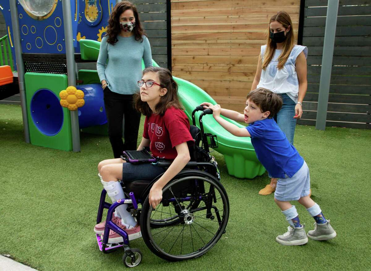 Jack Grodin pushes Avery Reilly's wheelchair at the Caroline School as their mothers, Helena Reilly, left, and Amma Grodin, watch. The kids are honorary ambassadors for Easter Seals Greater Houston's Walk With Me.