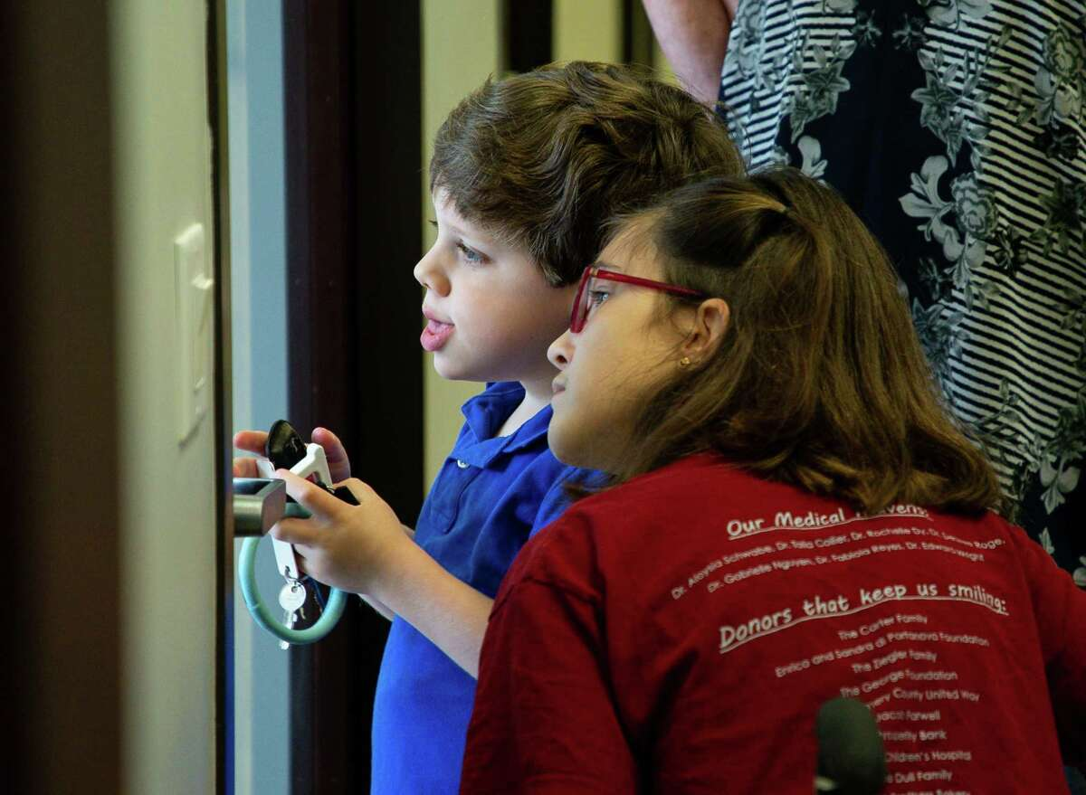 Jack Grodin, 5, and Avery Reilly, 13, look outside through a glass door at The Caroline School, on Wednesday, April 7, 2021, in Houston. Jack and Avery are ambassadors for the Easter Seals Greater Houston's Walk With Me event - which is celebrating its 10th anniversary - to raise money for those with disabilities.