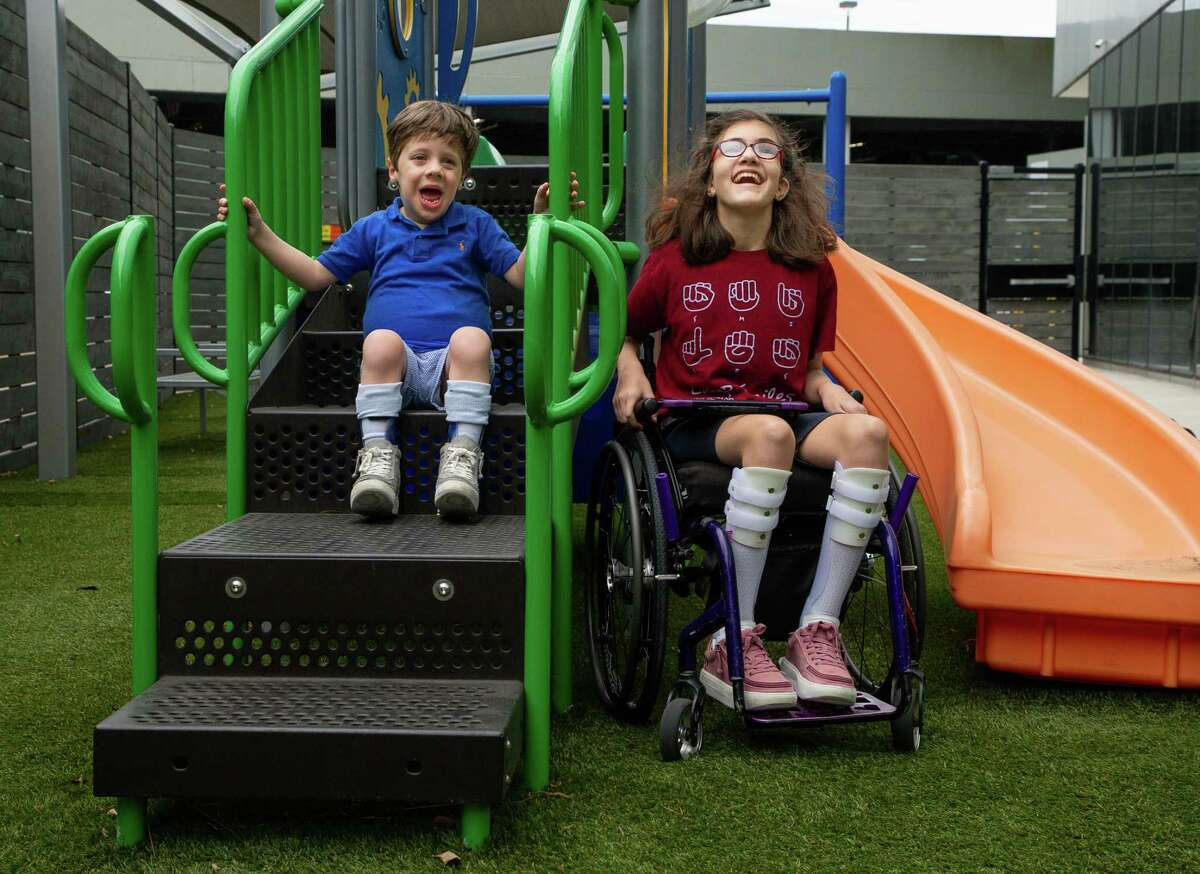 Jack Grodin, 5, and Avery Reilly, 13, pose for a photograph on the playground at The Caroline School, on Wednesday, April 7, 2021, in Houston. Jack and Avery are ambassadors for the Easter Seals Greater Houston's Walk With Me event - which is celebrating its 10th anniversary - to raise money for those with disabilities.