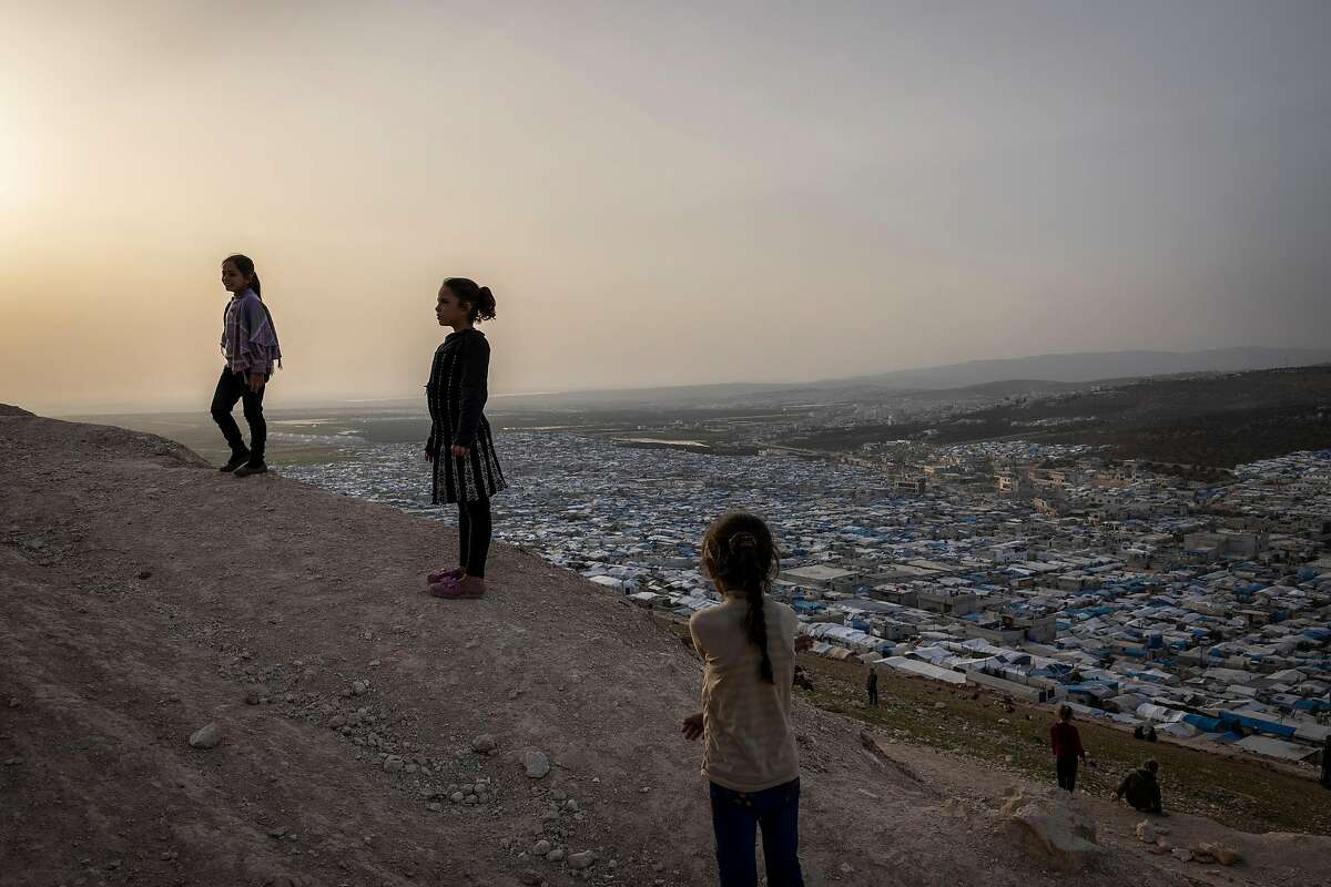 Children play on a hillside above a sprawling refugee camp near Idlib in northwestern Syria last month.