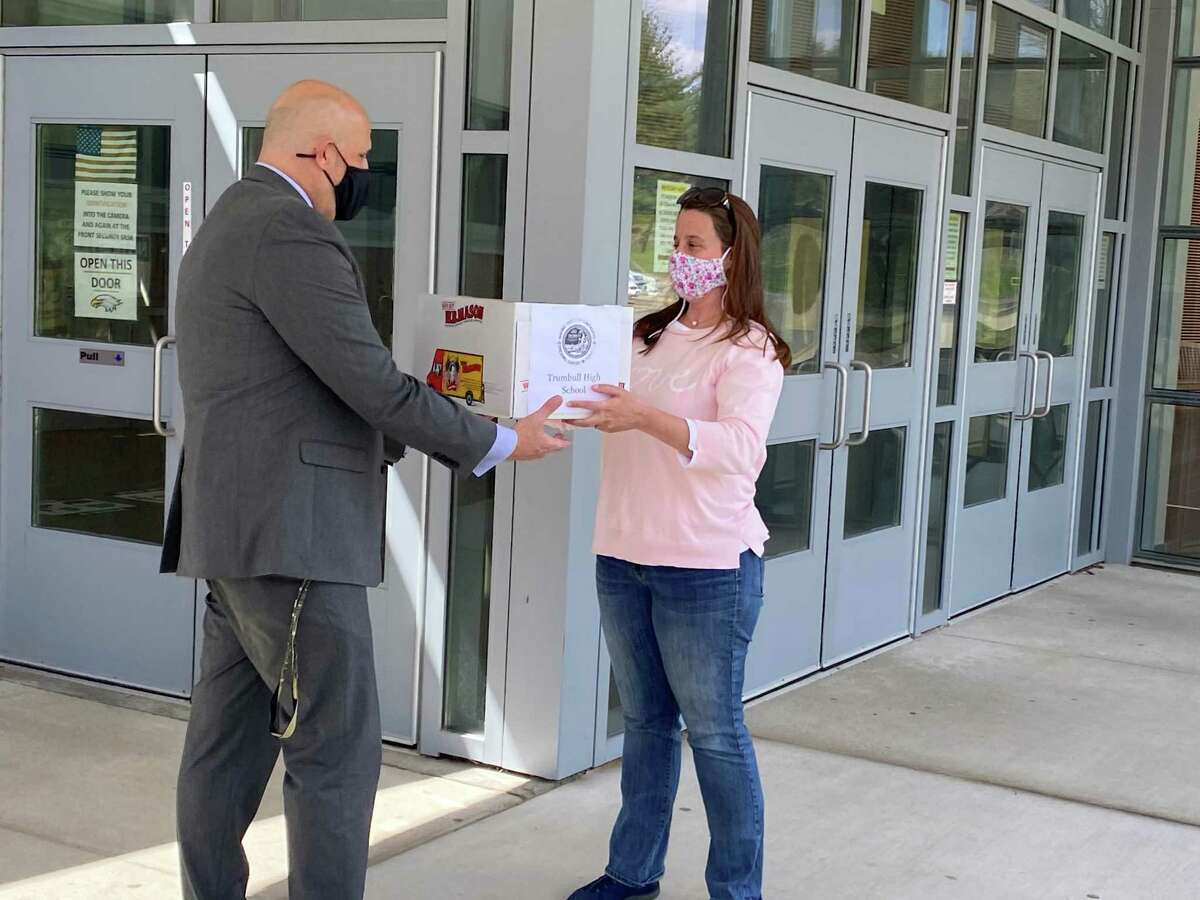 Trumbull High Principal Marc Guarino accepts a donation of gift cards to Trumbull restaurants from ImpacTrumbull president Jennifer Record.